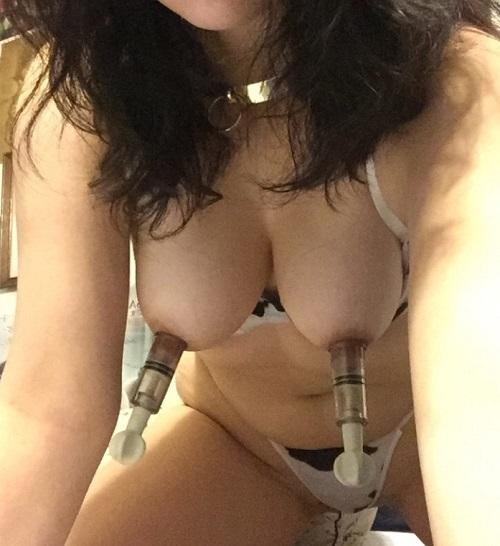 乳首吸引器で吸引されている女性